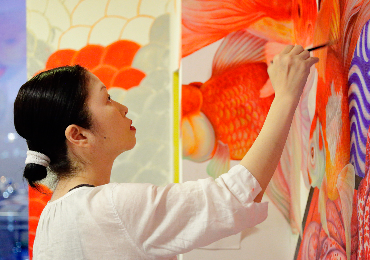 Artist Aki Narita paints with oils over wallpaper.