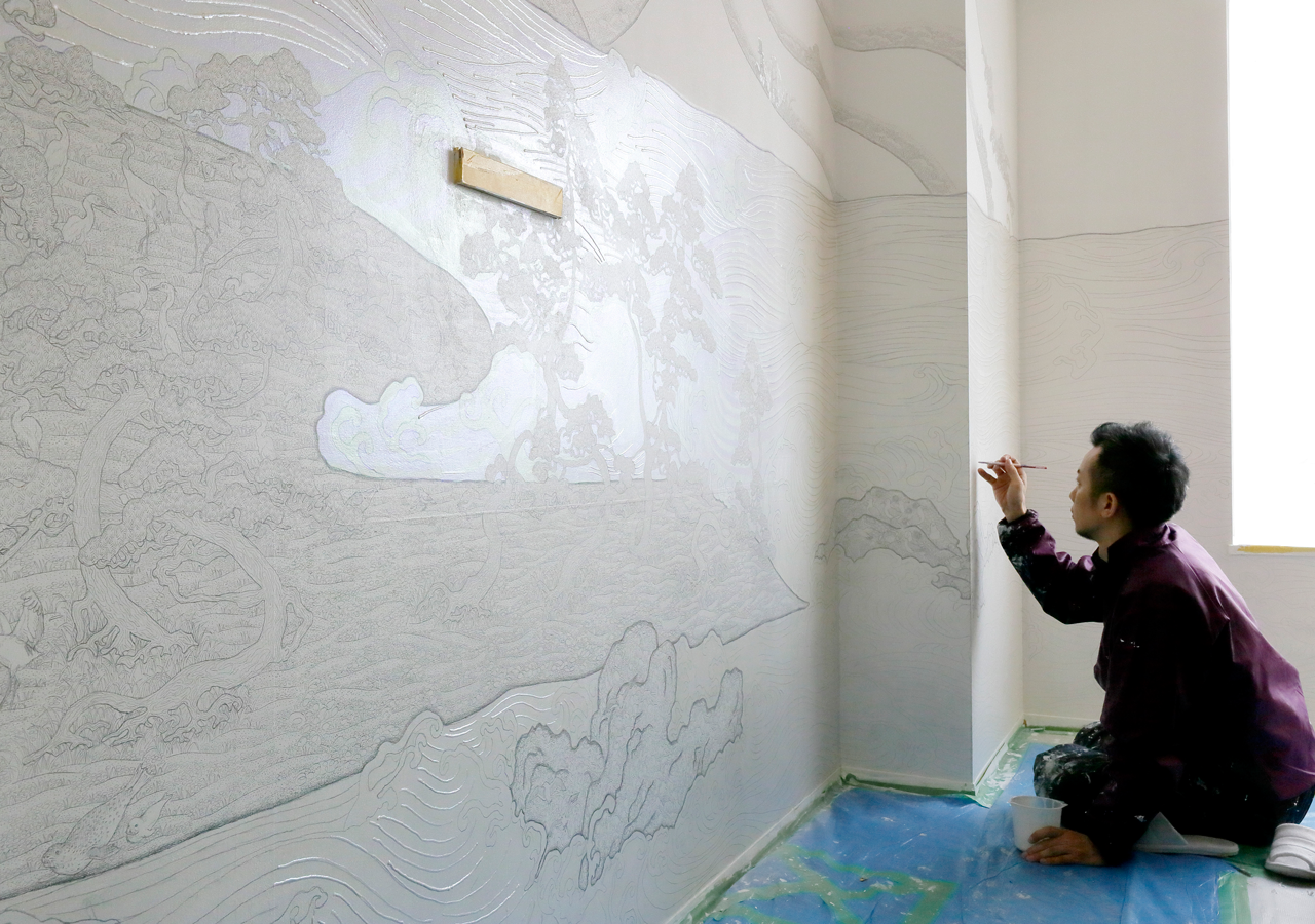 Artist Junji Yamada sketches his design on the walls of the guestroom.