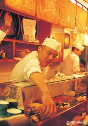 Sushi chef serving customers