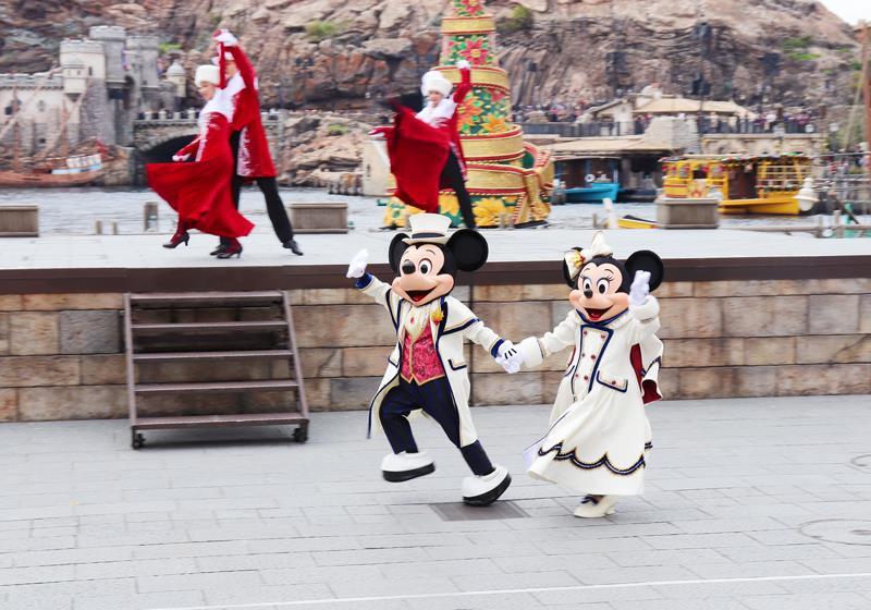 穿著白色豪華服裝的米奇與米妮手牽手登場。